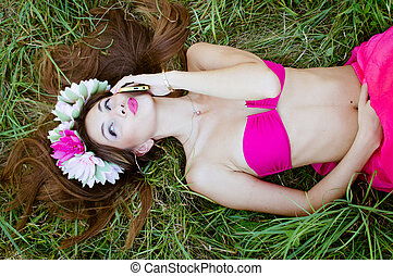 portrait of beautiful brunette young lady in pink bikini and flower crown having fun calling on mobile phone relaxing lying on green grass outdoors copy space background