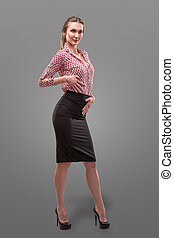 Portrait of beautiful business woman in a red shirt and black skirt with make-up skin foundation over grey background