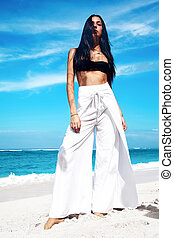 portrait of beautiful caucasian woman model with dark long hair in wide-leg classic pants  posing on summer beach with white sand on blue sky and ocean background