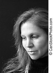 portrait of beautiful caucasian woman with long hair in black and white looking off to the side. side lighting