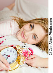 portrait of beautiful charming young woman blond girl happy smiling & looking at camera with an alarm clock in hand