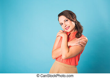 Portrait of beautiful cheerful smiling young woman on blue background with copy space