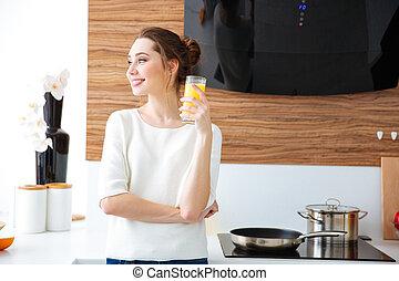 Portrait of beautiful cheerful woman drinking juice