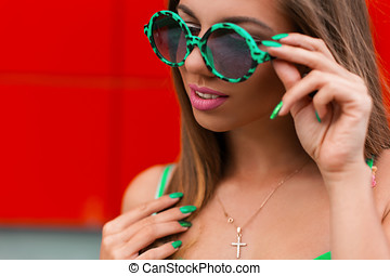 Portrait of beautiful cheerful woman with a smile in a stylish round green sunglasses on a red background.