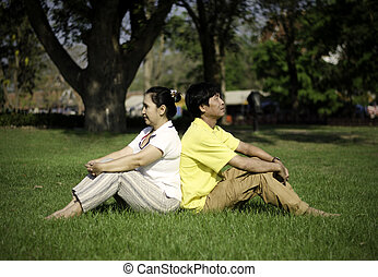 Portrait of beautiful couple sitting on ground in park