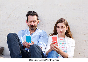 Portrait of beautiful couple sitting together holding cellphones