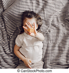 Portrait of beautiful cute little 3 years girl lying on bed in dress and looking at the camera