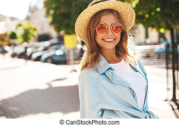 Portrait of beautiful cute smiling blond teenager model in summer hipster clothes posing on the street background.