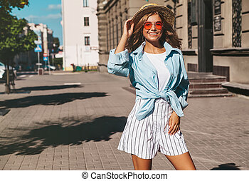 Portrait of beautiful cute smiling blond teenager model in summer hipster clothes posing on the street background