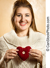 beautiful cute woman posing with knitted heart