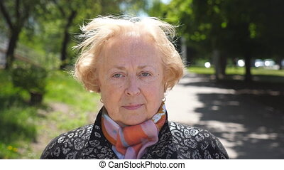Portrait of beautiful elderly woman seriously and pensive looking at camera. Senior caucasian lady of retirement age is standing in urban city background. Sight of grandmother outdoor. Close up.