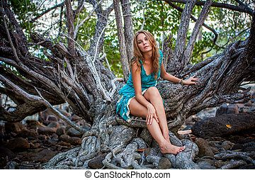 Portrait of beautiful elegant lady with dress in a green jungle rainforest