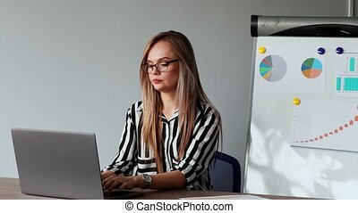 Portrait of beautiful European girl sitting at a laptop in the office with a white shirt on the background of graphs and tables