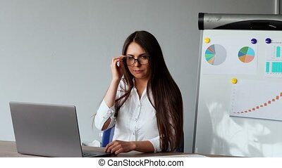 Portrait of beautiful European girl sitting at a laptop in the office with a white shirt on the background of graphs and tables. Looking at the camera