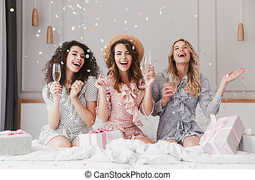 Portrait of beautiful excited women 20s wearing dresses celebrating bridal shower in posh apartment with champagne and falling confetti