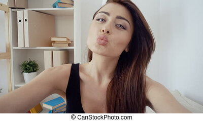 Portrait of beautiful exciting young woman in black top making selfie. Charming girl happy smiling on white indoor background.