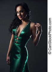 Portrait of beautiful fashion model in green dress on grey