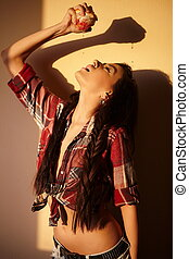portrait of beautiful fashion sexy brunette girl in jeans and colorful shirt  behind sunset squash orange indoors