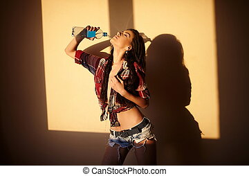 portrait of beautiful fashion sexy brunette girl in jeans and colorful shirt  behind sunset with bottle water  indoors
