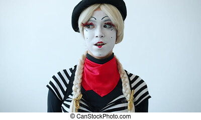 Portrait of beautiful female mime in bright costume rolling eyes and smiling standing alone on white background. Facial expressions and people concept.