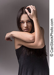 Portrait of beautiful female model on grey background. abstract woman holding hands close to head looking into camera