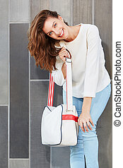 beautiful female model posing with a handbag