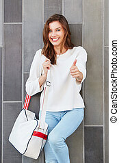 female model with handbag giving thumbs up against a wall