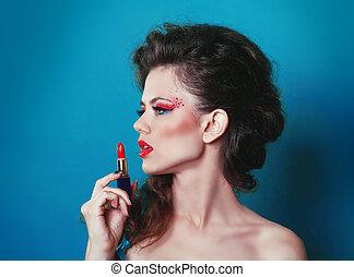 Portrait of beautiful female model with red lipstick over blue
