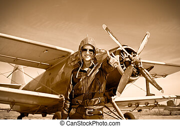 Portrait of beautiful female pilot with plane behind.
