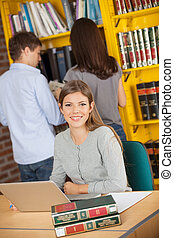 Portrait of beautiful female student with laptop while friends standing in background at college library