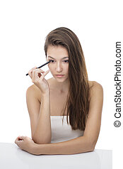 beautiful girl applying eyeliner