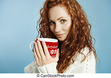 Portrait of beautiful girl drinking hot tea or coffee