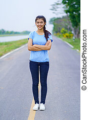 Portrait of beautiful girl in blue t-shirt and jeans standing in the outdoors