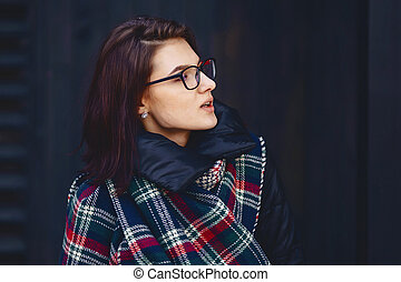 portrait of beautiful girl in eyeglasses and a scarf against a wooden wall