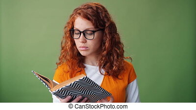 Portrait of beautiful girl in glasses reading book on green background