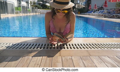 Portrait of beautiful girl in hat and sunglasses reading book at pool. Young woman relaxing at warm sunny day during vacation. Summer holiday concept. Front view Close up Slow motion