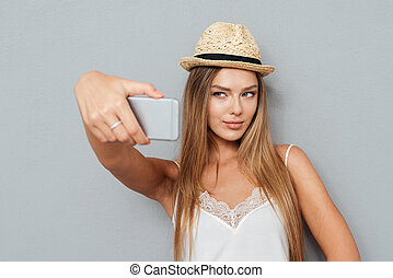 Portrait of beautiful girl in hat making selfie with...