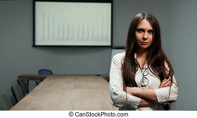 Portrait of beautiful girl in office clothes standing in conference room with glasses looking at camera