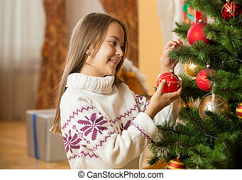 Portrait of beautiful girl in sweater decorating Christmas tree