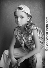 Portrait of  beautiful girl in  t-shirt and trousers in the inverted cap room beforehand black and white photography