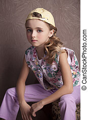 Portrait of beautiful girl in  t-shirt and trousers in the inverted cap room beforehand