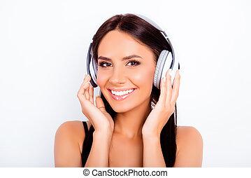 Portrait of beautiful girl listening music in white headphones