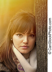 Portrait of beautiful girl outdoors leaning on a tree