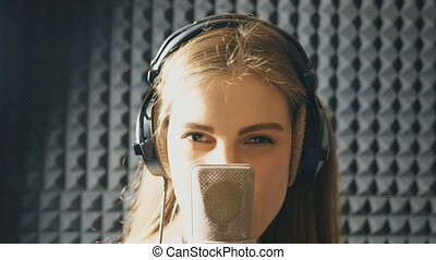 Portrait of beautiful girl singing in sound studio. Young singer emotionally recording new song. Lady sings to microphone. Working of creative musician. Show business concept. Slow motion Close up