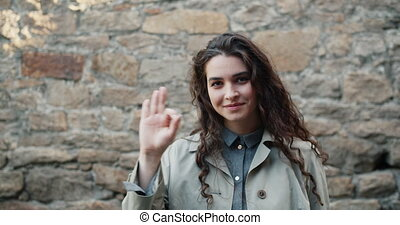 Portrait of beautiful girl student showing OK hand gesture...