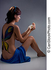 portrait of beautiful girl with bodyart sitting and looking...
