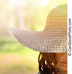 Portrait of beautiful girl with curled hair and straw hat in ret