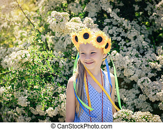 Portrait of beautiful girl with flowers of sunflowers on his head.