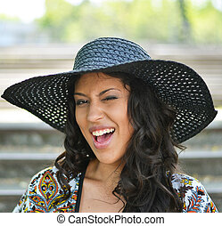 Portrait of beautiful girl with hat winking