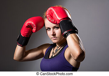Portrait of beautiful girl with red boxing gloves, aggressive an